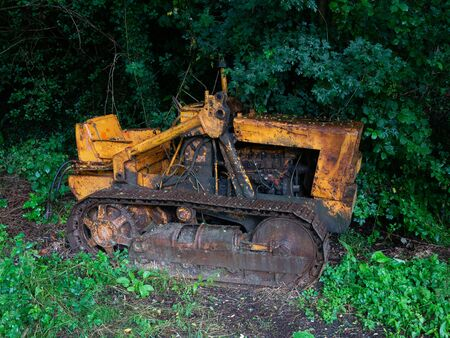 old yellow rusty track tractor abandoned and surrounded by vegetation