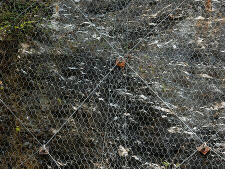 detail of metal mesh and wires used to protect mountain roads from landslide and rockfall Archivio Fotografico