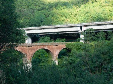 modern concrete bridge and vintage bricks bridge surrounded by trees Archivio Fotografico