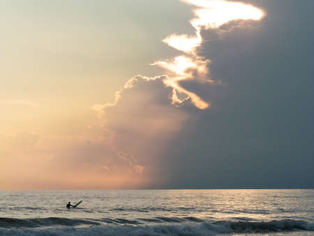 surfer waiting for waves in a overcast evening, the sun's rays filter through the clouds