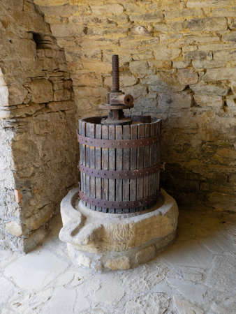 old wine press made of wood, metal and stone used to crush the bunches of grapes, stone wall background