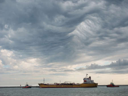 chemical tanker ship enter the port with tugboats, under a stormy sky