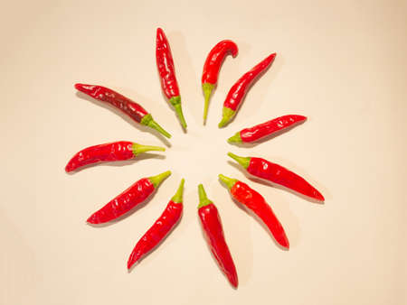 hot ripe organic chili peppers arranged in a circle, light background