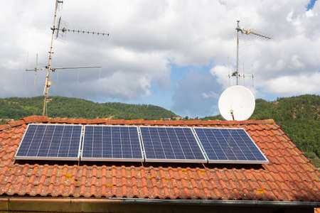 solar panels and antennas on the roof of a house in the countryside. hills covered with woods in the background