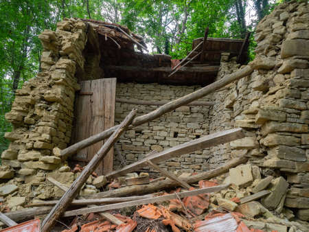 debris and rubble of an old stone house collapsed in the woods