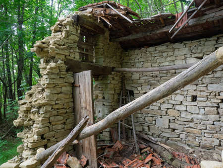 small old stone house in the woods collapsed; debris and rubble scattered everywhere