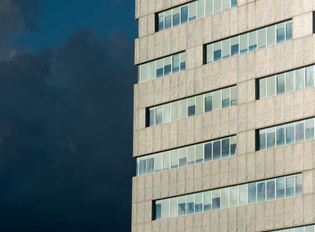 detail of a modern office building, dark blue cloudy sky in backround