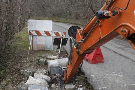 empedrado: excavadora excavar un camino pavimentado Foto de archivo