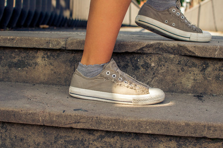 step up: sporty woman step up on stairs with sneakers Stock Photo