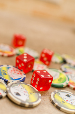 red dice and scattered casino tokens