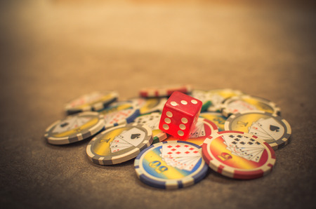 a red dice on casino tokens Archivio Fotografico