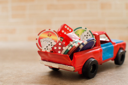 dice and casino tokens stacked on a toy car