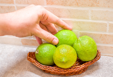unripe: hand take unripe lemons lime