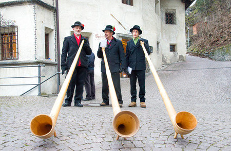 perform: Alphorn players perform in the historic center of Brunico Editorial