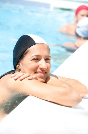 swimming cap: woman pool edge smile wear black swimming cap Stock Photo