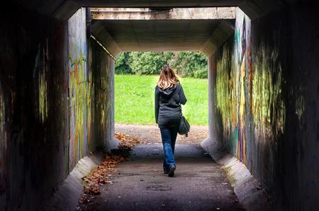 woman walk alone through dangerous dark underpass
