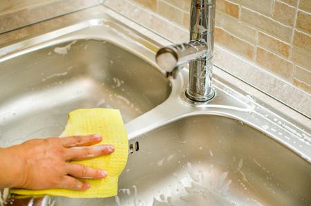 grifos: mano de la mujer que hace tareas de limpieza moderna gris fregadero de la cocina Foto de archivo
