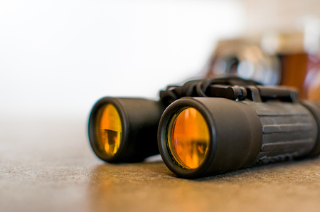 hand held: binoculars yellow mirror lens closeup background texture white isolated Stock Photo