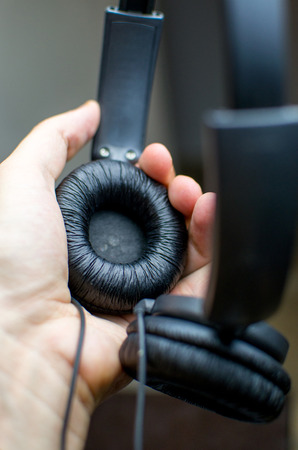 wired: male hand take wired headphones Stock Photo