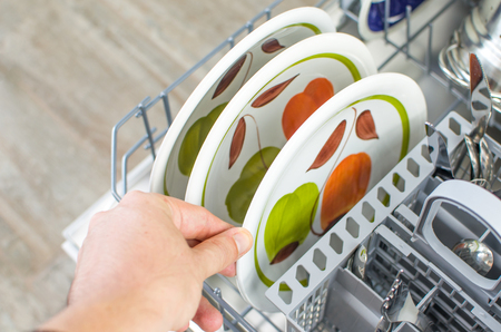 pull out: chores, take clean dishes from the dishwasher Stock Photo