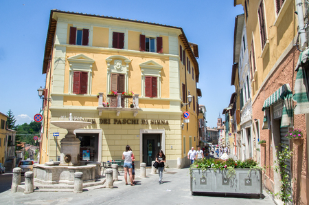 asciano: Asciano, Italy, May 31, 2015 - People stroll in the small square with fountain Editorial