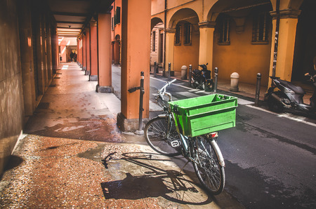 portico: Bologna, Italy, April 25 2016: parked bicycle on narrow street along an empty portico