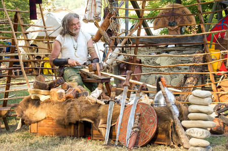 trinchante: Monterenzio, Italy, 09 July 2016 - a wood carver craftsman realize swords and shields during a Celtic Festival Editorial