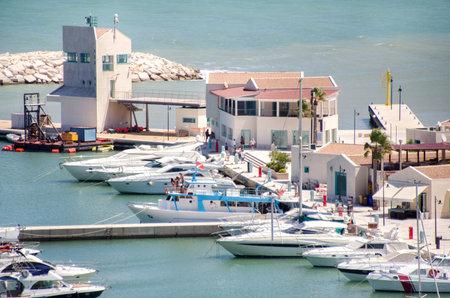 rodi garganico: Rodi Garganico, Italy, August 2, 2016: Boats moored at the marina and people that take a walk on the pier