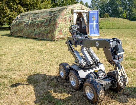 defuse: Ferrara, Italy 16 September 2016 - a  bomb disposal robot unit used by the Army to  defuse bombs and a military green curtain during an exposition of the Italian Air Force Army