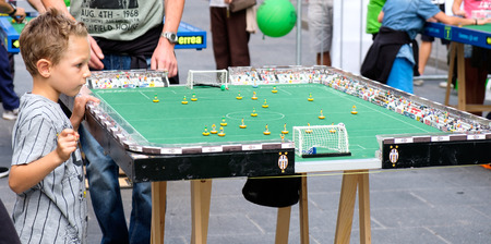 simulations: Bologna, Italy, 18 September 2016: A child focusing on a Subbuteo game Editorial
