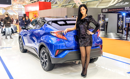 chr: Bologna, Italy, Dec 03 2016 - a black haired elegant model posing leaning to a Toyota C-HR car during the Motor Show 2016 in Bologna