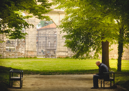 Stra, Italy, 25 Apr 2017 - aged man sitting in loneliness on a park banch in the shade of trees