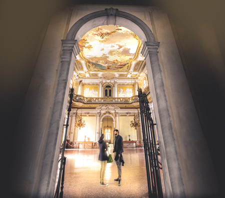 Stra, Italy, 25 April 2017: a young couple chat inside a large and regal hall of Villa Pisani Editorial