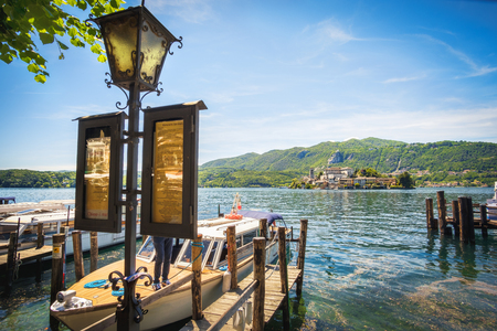 orta: Orta San Giulio, Italy, 21 May 2017 - The Orta lake boat docks and lamppost with timetables to the San Giulio island