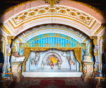 Stresa, Italy, May 22 2017 - an antique puppetry theatre decorated with a golden curtain