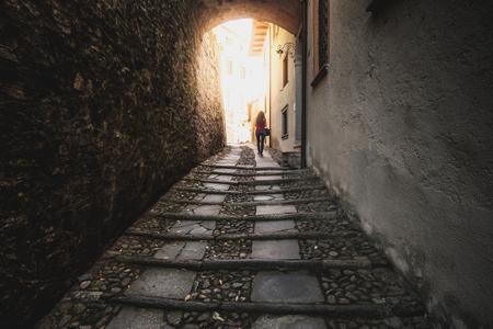 orta: woman walk dark street narrow alley Stock Photo