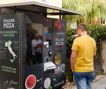 Brunico, Italy, 12 aug 2017- tourists try a pizza vending machine