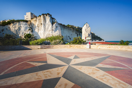 daunia: lungomare (seafront) of Vieste with a windrose symbol designed on the ground and the Pizzomunno white rock on background Stock Photo