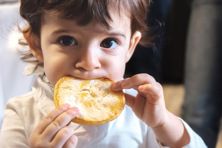 baby child eat carbohydrates -  newborn eating face closeup portrait - unhealthy diet for kids