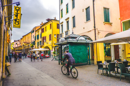 イタリアでの日常生活。通りの緑のニューススタンドのキオスクを通るパドヴァの中央道の1つを横切る自転車のビジネスマン (パドヴァ、イタリア 報道画像
