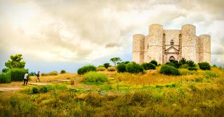couple climb steps in a natural yellow landscape to reach  Castel del Monte in Apulia - Andria Trani province - Italy