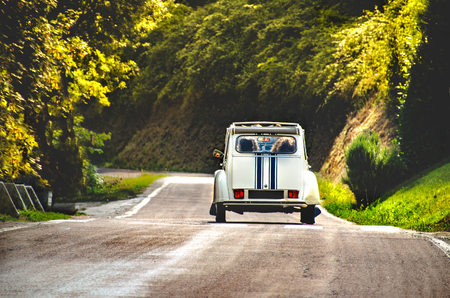 vintage car country winding road back view friends road trip