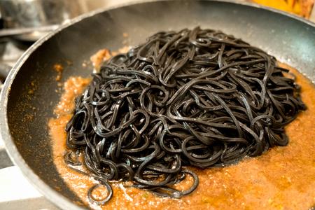 black pasta squid ink in a pan - italian taglierini al nero di seppia