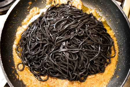 black pasta squid ink pan up view italian taglierini al nero di seppia Stock Photo