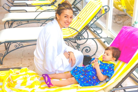 Mother and baby spa child wellness relaxing on deckchair drinking fruit juice