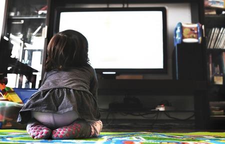 pasgeboren baby tv kijken op het tapijt in de woonkamer sokken achteraanzicht Stockfoto