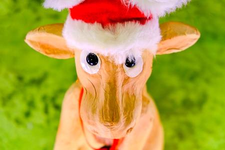 reindeer with christmas hat ornament character face portrait looking at camera toy decoration