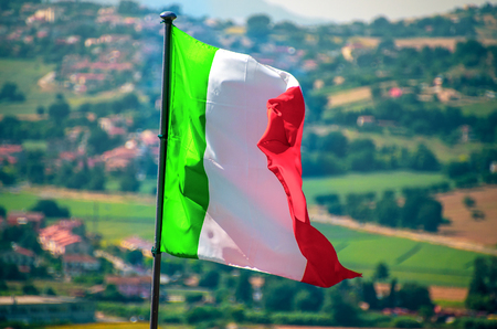 waving italian flag wave countryside background Stock Photo