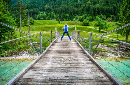 happy distant woman jump of a wooden pedestrian bridge footbridge over river Soca in Slovenia in  wild nature background