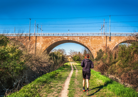 man jogging urban park bridge railway path trail in the city background